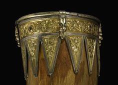 Silver-gilt drinking-horn mounts: bird head terminal with ribbing; rim band with human and rosette motifs; nielloed; twelve vandykes.