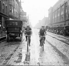 CITY LIFE: Image of two boys riding bikes along a street in the rain during a street car strike in Chicago, Illinois. It is not easy to ride on wet cobblestone or across trolley tracks.