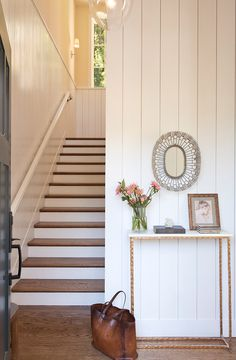 source: Braun Adams website save:    share:         Chic foyer features a vertical shiplap wall lined with a brass and marble console table under an oval wire mirror.