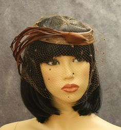 Hat of brown woven straw with hand-made bird of feathers at front; hat is covered with veil accented with chenille dots.