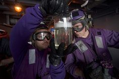 Aviation Boatswain's Mate (Fuel) 1st Class Jesus Trevino (left) and Aviation Boatswain's Mate (Fuel) Airman Chase Clausen inspect JP-5 fuel on a fueling sponson aboard the aircraft carrier USS Dwight D. Eisenhower (CVN 69), the flagship of the Eisenhower Carrier Strike Group, during a replenishment-at-sea with the Military Sealift Command fleet replenishment oiler USNS Leroy Grumman (T-AO 195).