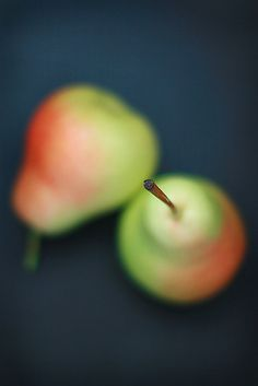 Shallow Depth of field.  The eye moves towards the edge of the pear. Overall , the photo is pretty balanced the eye does not move towards one directly. However, if not, the eyes move towards the focus part of the pear.  Color: there is contrast between the red and green part of the pear. The color stands out because of the dark navy background. There is no movement