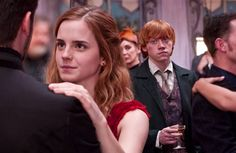 Viktor Krum and Hermione dancing at Bill and Fleur's wedding while Ron looks on with jealousy.