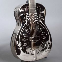 """National's first 14-fret metal-body guitar, a Style O, patterned after a 1937 National. The body is nickel plated brass with a domed back, f-holes, etched Hawaiian scenes, and a """"chicken foot"""" pattern coverplate. The neck is maple with a dot inlaid, bound ebony fretboard, 2-way adjustable truss rod and solid headstock with a National banner style inlay. The power comes from a National swirl-pattern spun cone with biscuit bridge. Includes a shaped wooden hardshell case."""