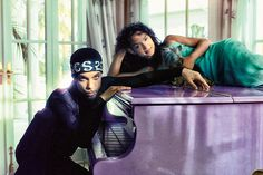 American singer-songwriter, multi-instrumentalist and record producer, Prince sits on a piano with his wife Mayte Garcia, 1999.