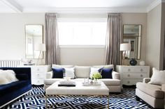 Amazing living room features an ivory linen sofa adorned with navy velvet pillows under a window dressed in gray silk drapery panels flanked by Bungalow 5 Jacqui Large 4 Drawer chests topped with gold lamps under tall gold mirrors. A navy velvet sofa, Jonathan Adler Lampert Sofa, faces a white leather tufted ottoman coffee table atop a navy Greek key rug