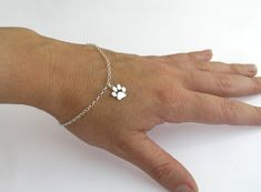 Sterling silver bracelet with a handmade, shiny paw print charm. A lovely gift idea for cats and dogs lovers.  The paw size is about 0.9 by 0.9 cm/ 0.35 by 0.35 inch. The silver chain is 19 cm/ 7.5 inch long. If you like to have it in a different length, or add an extension, please let me know and I will change it for you (for no extra charge).  I also have paw print earrings: https://www.etsy.com/listing/105870008/paws-print-earrings-silver-stud-earrings?ref=shop_home_feat  A paw print…