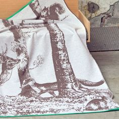 Country Living Editor Says  Bring a touch of charming rustic style to your home with this distinctive woodland throw, featuring an owl, squirrel, deer, fox and rabbit.   Printed in tones of grey, with an eye-catching emerald-green edging, it is made from a soft cotton-mix fleece.   A matching green squirrel cushion is available.  Machine washable.  Measurements: 140cm x 200cm.