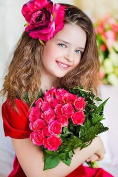 Beautiful girl with a rose in her hair carrying a bouquet of flowers.