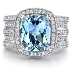 Large blue topaz framed by diamonds and set in a 5 band diamond ring