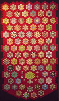 great fussy cutting - and I love the red background! - hexagon quilt
