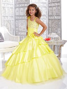 Stunning Tiffany Glitz Children Pageant Dress 33422. This taffeta pageant dress displays one shoulder strap with a floral applique, double straps in the other shoulder, asymmetric neckline, and beaded and pleated bodice. Completing the look of this pageant dress is a tiered ball gown skirt. Make this beautiful dress perfect for your 2012 pageant. Available in Yellow, Crystal Ice and Purple.