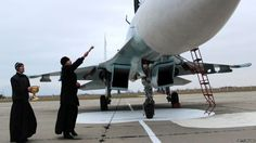 A Russian Orthodox priest blesses a fighter jet