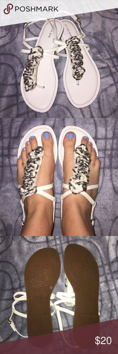 Gianna Bini cute summery sandals!! These white sandals are perfect for weddings, dances, work, church, dates and could even go for a causal event! The top fancy part is silvery/charcoal colored and is so fun! There is a small purple dot at the top of the left shoe, but barely noticeable when worn! Great condition and no scuffs on the sole! Gianni Bini Shoes Sandals