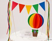 Above the Clouds : Colorful Rainbow Hot Air Balloon Cake Topper with Lacy Buntings Ribbon Accents - Red Pink Orange Yellow Green Blue Purple. $25.00, via Etsy.
