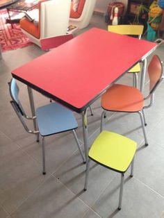 Table et chaises vintage en formica des années 60 : une grande table rouge avec rallonge, et deux tiroirs. Quatre chaises : rouge, jaune, orange et bleu. Un tabouret vert. Un ensemble en bon état, couleur pop, années 60 idéal pour déco vintage, loft...