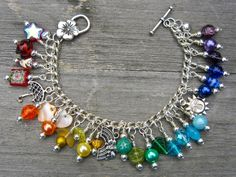 """This is once of my consistent best sellers, it's such a happy little bracelet that it makes everyone smile :o) A variety of glass, shell and ceramic beads adorn a silver-plated chain of approx. 7.5"""", and there is a small jingle on each end. Unless you want that size adjusted (please ask if you do) there are four beads of each colour of the rainbow attached to it. There are three silver tone charms included - an umbrella, a rainbow peeking from behind a cloud and a sun.   $25.00"""