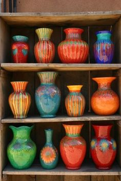 Pottery...love the bright cheerful colors. The arrangement is stunning, too. LOVE the primitive shelves. PERFECT for the pottery.