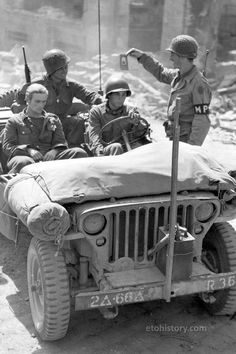 John A. Cereza and Pvt. Albert Del Balzo (Recon Co, Armd Rgt) ask directions from PFC Hobart MacMillian Inf Div) where they can deposit a German sniper collected in Sourdeval, France. Photo by Joseph A. Military Jeep, Willys Mb, Ww2 Photos, Military Pictures, Jeep Wrangler Tj, Army Vehicles, War Photography, Jeep Models, American Soldiers