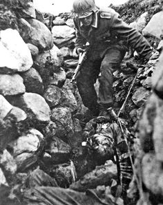 As the 100th Infantry Division fights its way through towards the tractor factory on 4 October the Germans overrun a number of Russian defensive positions. Here a German soldier moves stealthily through a captured trench and climbs over the bodies of dead Russian soldiers.