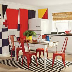 This room's vibrant kitchenette is furnished with a painted breakfast table, cherry red metal chairs, and a striped rug.