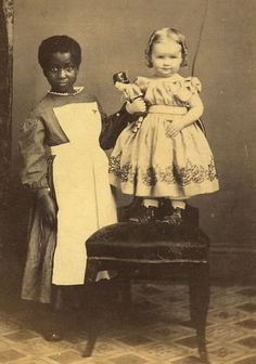 Very young nurse with baby girl. The picture illustrates the embarrassing history of slavery, even small children being taken away from their families and being used as unpaid laborers in white families.