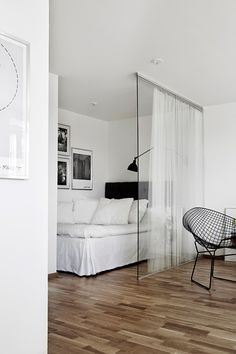 Glass wall and curtains divide the bedroom from the living room. Clever idea for small studios!