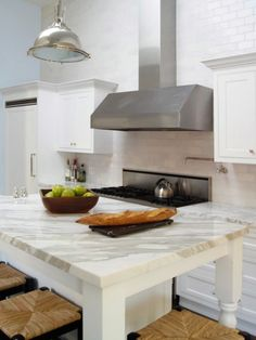The Italian Calcutta Gold marble countertops make this transitional kitchen a great place to gather. The polished nickel pendants from Restoration Hardware add sheen and enhance the height of the ceilings. This white chef's kitchen is accented by the pale blue walls, creating a refreshing space to enjoy a meal in.