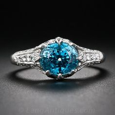 An ultra-deep, electric Caribbean-blue zircon radiates from within a gorgeous platinum and diamond ring created in homage to the timeless Art Deco styles of the The entrancing gemstone is embraced on four sides by elegantly fashioned diamond-se Gems Jewelry, Gemstone Jewelry, Jewelery, Jewellery Box, Antique Jewelry, Vintage Jewelry, Antique Diamond Rings, Man Made Diamonds, Blue Zircon