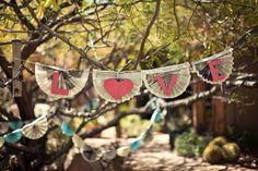"DIY newspaper ""Love"" garland at vintage-inspired wedding. Spotted on ruffledblog.com"