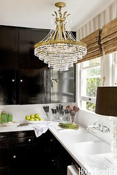 """A crystal chandelier and high-gloss kitchen cabinets painted Farrow & Ball's Pitch Black """"remind me of Paris apartments and grand French style,"""" Tobin says. Read more: High Gloss Black Kitchen Cabinets - Modern Farmhouse Design - House Beautiful Black Gloss Kitchen, High Gloss Kitchen Cabinets, Black Cabinets, Painting Kitchen Cabinets, Glossy Kitchen, Wood Cabinets, Beautiful Kitchens, Beautiful Homes, House Beautiful"""