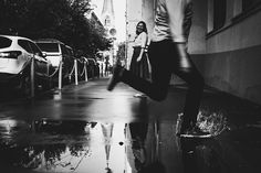 Девушка стоит сзади Парень пробегает через лужи , делая небольшой прыжок. Сняты его ноги. Она полностью. Снимать снизу