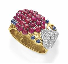 A RETRO DIAMOND, RUBY AND SAPPHIRE BANGLE BRACELET  The wide gold hinged bangle set on top with with a scrolling design of ruby and sapphire cabochons, to the circular and baguette-cut diamond leaf, mounted in yellow and white gold, circa 1945