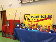 Candy table for truck theme party in red yellow & blue colors. Semi-Truck made from cardboard boxes with truck logo of childs last name. Truck stacks cardboard tubes wrapped in tinfoil