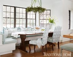 Even Christmas Eve dinner is enjoyed at the kitchen banquette, where the pendant light sports a festive wreath, and a bevy of blue fabrics, used for cushions, pillows, and upholstered chairs there and at a table in the adjoining family room, introduces slight color that doesn't rival the family's frenzy.