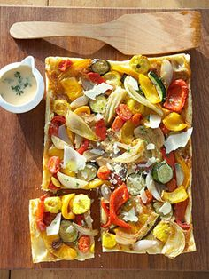 This savory and simple appetizer tart uses easy puff pastry as its base. Roasted vegetables and flavor-packed Parmesan cheese top it off.