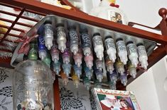 Magnets on bottom of bottles, and then they can always be ready to use.  Great idea for a craft room.