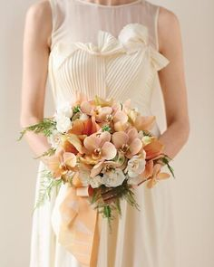 Orchids and amaryllis add peach accents to this feminine bouquet.another bouquet Matthew Robbins made for Martha Stewart Weddings. Orchid Bouquet Wedding, Peach Bouquet, Ribbon Bouquet, Spring Bouquet, Peach Flowers, Pastel Bouquet, Boquet, Peach Gown, Wedding Flowers