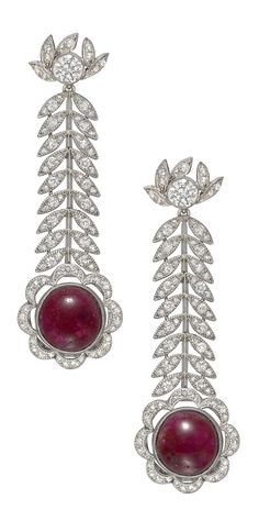A pair of Belle Epoque platinum, cabochon ruby and diamond earrings, circa 1910. Each featuring a circular-shaped cabochon ruby with a scalloped diamond-set surround, suspended from a diamond-set foliate motif chain, in platinum.