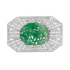 Art Deco Platinum, Carved Jade and Diamond Brooch 18 kt. white gold, the octagon plaque pierced with a radiating design centering one oval carved jade approximately 22.0 x 27.0 x 4.5 mm., set throughout with rose-cut diamonds, with French assay marks and maker's mark, partially obscured, circa 1920, approximately 11 dwt.