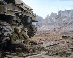 US 3AD soldiers, Cpl. James L. Gregory and T/5 Omer G. Taylor of 'C' Company, 1st Battalion, 36th Armored Infantry Regiment, 3rd Armored Division seek shelter behind a M-4 Sherman tank while under German Artillery bombardment at Geich, near Düren, Germany, on December 11 1944. (Nb. Both soldiers survived the war) (T/5 = Technician Fifth Grade) (Source - US National Archives and Records Administration - 531225) (Colorized by Jared Enos from the USA)