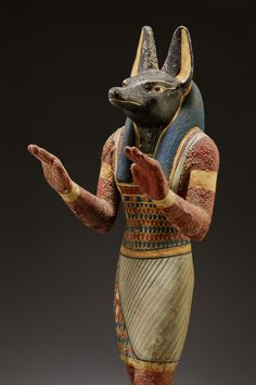 ~ Statuette of Anubis. Period: Ptolemaic Period Date: 332-30 B.C. Place of origin: Egypt Medium: Plastered and painted wood.