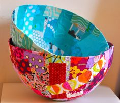 super cute idea for fabric. bowls made by wrapping papier mache around the fat end of a balloon, allowing it to dry and then gluing strips of fabric over the form. from bread and buttons