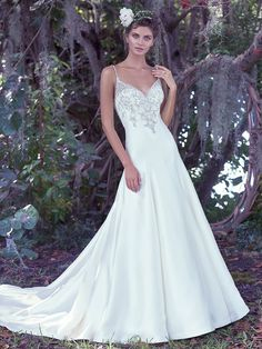 Maggie Sottero - KIMBERLY, Refined elegance is found in this embellished Elodie mikado A-Line wedding dress with a deep V-neckline. Glimmering Swarovski crystals generously adorn the fitted bodice, beaded spaghetti straps, and dramatic illusion back. Finished with crystal buttons over zipper closure.