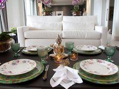 mesa posta com sousplat verde, prato branco floral, guardanapos de linho, argola dourada e buda e velas para decorar.