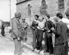 Dans le bourg de Beauvain, jeunes gens discutant avec le Major General Manton Sprague Eddy commandant de la 9th US Infantry Division. En arrière plan l'église Saint Léonard. Beauvain est libérée le 16 août 1944 et le PC de la division est le 17 à 1 mi.SE de Le Grais (Beauvain est bien au SE de Le Grais mais à 4 mi. !)