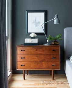"""Modern bedroom design featuring dark gray walls, medium gray curtains, and a light gray upholstered bed that pairs beautifully with the mid-century modern wood chest of drawers bedside table - Bedroom Ideas & Decor -  Wall paint: Benjamin Moore 2121-10 """"Steel Wool"""""""