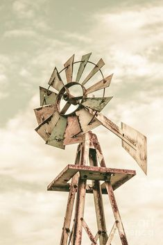 Weathered and vintage Aermotor windmill utilising wind energy to pump water for cattle on an outback Australian farm. Agricultural architecture by Ryan Jorgensen