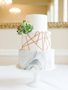 Marbled cake with rose gold geometric details and sugar succulent cluster. Image copyright Blue Rose Photography.