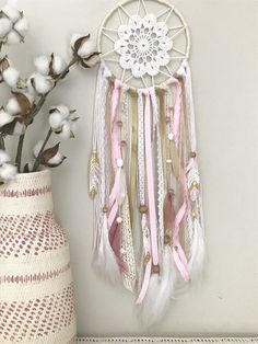 """This beautiful dream catcher is the perfect addition to your pink and gold nursery or bedroom. It is made up of different pink, gold, white and ivory ribbons, lace and yarn. This dream catcher has many details including pink and white stones, natural feathers and 3 unique hand painted feathers with boho designs. Measuring at 6"""" wide by 22"""" long, this dreamer is sure to keep the bad dreams away, leaving room for only the sweet ones! To customize details, visit www.shopwildcotton.com"""